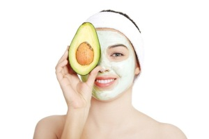Young woman with facial mask and avocado